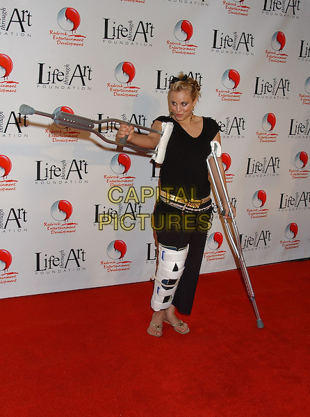 KALEY CUOCO.The 2nd Annual 'Red Party' to Benefit The Life Through Art Foundation held at the Shrine Auditorium. .December 4th, 2004.full length dangling gold hoop earrings, black top, trousers, cast,  crutches, support, injury, flip flops, pointing, gesture.www.capitalpictures.com.sales@capitalpictures.com.© Capital Pictures.