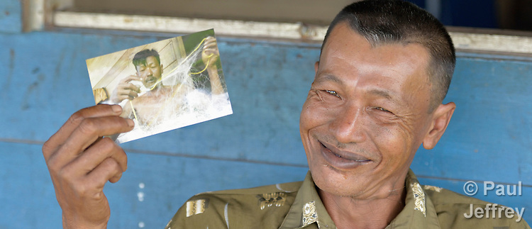 In 2014, Irman Baeha holds a photo of himself taken in 2007. He is a fisherman in the village of Moawo on the Indonesian island of Nias. His house was flattened by the 2004 tsunami, and he and his family later moved into a new house constructed by YEU, a member of the ACT Alliance. Yeu built 72 houses in the community. With foundations of cement, they are more resilient than the pre-tsunami houses which were built entirely of wood. YEU also helped the community members restart their local economy, and assisted the community as it planted mangroves to protect the shoreline and revitalize their fishing industry. Nias also suffered a devastating earthquake in 2005.