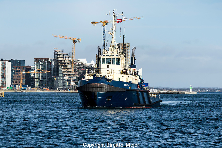 """The tug vessel """"fenja"""" that sails with Danish Flag, sailing into the port in Aarhus Denmark, with the architecture and buildings in process at Aarhus Ø in the background"""
