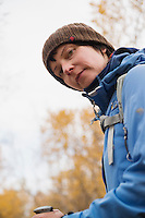 Portrait of female hiker in yellow Autumn birch forest along Kungsleden trail, near Abisko, Lappland, Sweden