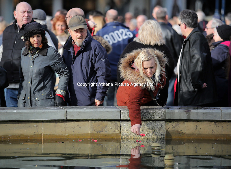 Pictured: A woman deposits poppies in the fountain Friday 11 November 2016<br />Re: Remembrance Day service at Castle Square Gardens in Swansea, south Wales, UK.