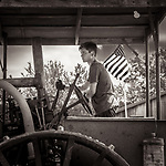 THIS IS AMERICA -- meaning no offense to the music video that is so popular now, but I beg to differ. A young man driving an antique tractor at the Rock River Threstheree in Edgerton, Wisconsin, USA.