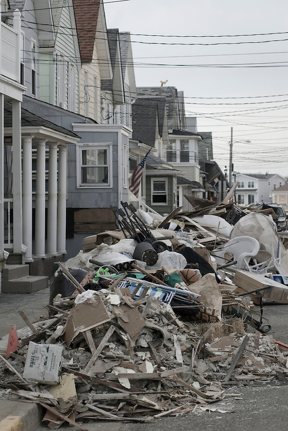 Flooded by Hurricane Sandy houses with piles of debris in front of them on the main street of Sea Bright, NY.