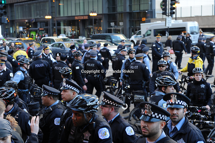 Police block protesters calling on Chicago Mayor Rahm Emanuel to resign on Randolph Street at Michigan Avenue in the Loop in Chicago, Illinois on December 9, 2015.  Emanuel offered a historic apology for the police killing of Laquan McDonald and police brutality and racial profiling generally -- without using those words -- in front of the City Council in the morning.