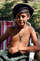 URUGUAY, people at horse riding contest, boy with cross / Menschen bei einem Pferderennen am Wochenende, Junge mit Kreuz