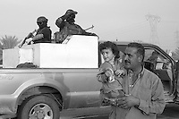 An Iraqi man carries a young girl after she has received sweets from private security operators from the British company ArmorGroup escorting a supply convoy near Baghdad, Iraq on October 20, 2006.  The coalition forces and civilian administration in Iraq depend heavily on thousands of controversial security contractors to support their reconstruction efforts and military operations.