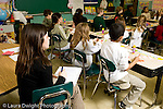 Education Elementary school Grade 2 student teacher making observation of class sitting on side with pad and pen horizontal