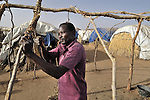 A newly arrived resident of a displaced camp outside the Darfur village of Garsila constructs a shelter for his family.