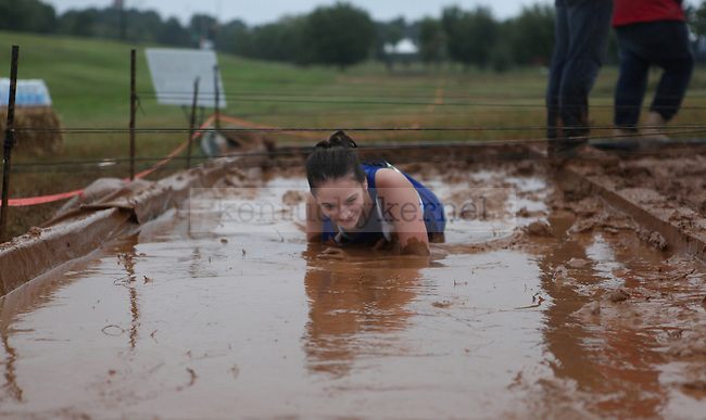 Amanda Dentinger, 18, crawls through a mud pit during the 2013 Bluegrass Mud Race at Commonwealth Stadium in Lexington, Ky., on Friday, September 20, 2013. Photo by Adam Pennavaria | Staff