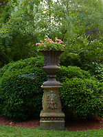 A stone urn on a plinth planted with pink flowers stands amongst the shrubbery.
