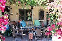 An outdoor seating area on the covered terrace features wooden African furniture and is surrounded with bougainvillea and jasmine