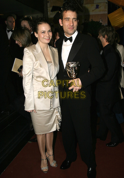 SARAH JANE FENTON & CLIVE OWEN.Official BAFTA Aftershow Dinner Party, .Grosvenor House, Park lane, London, .February 12th 2005..full length trophy award husband wife married.Ref: AH.www.capitalpictures.com.sales@capitalpictures.com.©Capital Pictures.