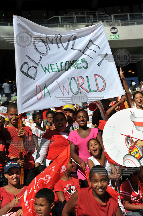Fans at the opening match at Cape Town's new 2010 FIFA World Cup football stadium. Blomvlei is a suburb of the city. 20,000 fans flocked to the stadium for its first public event since completion in December 2009. The stadium seats 68,000 and the first test event was used to check that all systems, transport, security, staffing and logistics worked satisfactorily.
