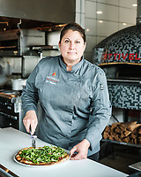 Chef Elise Wiggins works on a pizza at Cattivella in Denver, Colorado, Wednesday, August 10, 2017. She is making a pizza with grilled asparagus, arugula, garlic, evoo, prosciutto, fontina, and truffle oil.<br /> <br /> Photo by Matt Nager