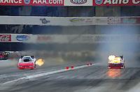 Nov. 11, 2011; Pomona, CA, USA; NHRA funny car driver Melanie Troxel (right) explodes an engine alongside Gary Densham during qualifying at the Auto Club Finals at Auto Club Raceway at Pomona. Mandatory Credit: Mark J. Rebilas-.