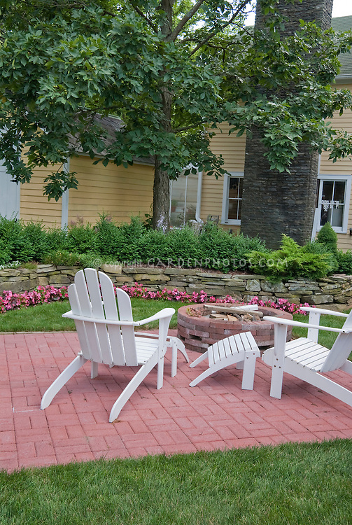 Brick patio in lawn grass with Adirondack white wooden furniture chairs, yellow house, stone wall with pink wax impatiens, fireplace firepit, raised beds, tree