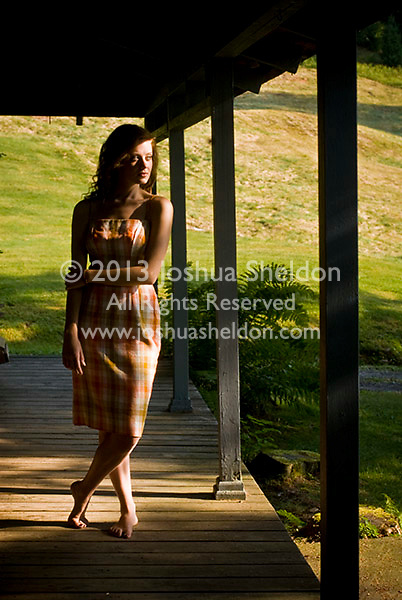 Young woman seen through screen door, standing on porch