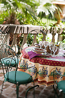 Wrought iron garden chairs with squab cushions and a table laid for lunch