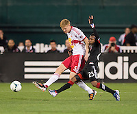 Marcos Sanchez (25) of D.C. United tries to tackle the ball away from Markus Holgersson (5) of New York Red Bulls during the game at RFK Stadium in Washington, DC.  New York Red Bulls defeated D.C. United, 2-0.