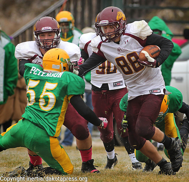 HILL CITY, SD - OCTOBER 29, 2013:  Dylan Gehm #88 of DeSmet tries to evade Hill City tackler Mitchell Peterson #55 during their 9AA high school playoff game against Tuesday in Hill City.  (Photo by Dick Carlson/Inertia)