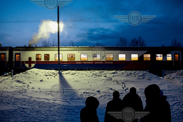 A view of the Matvei Mudrov train at dusk with a group of people standing in the snow outside. <br /> <br /> The Matvei Mudrov train is a medical train operated by Russian Railways along the course of the Baikal Amur Magistral (Baikal-Amur Mainline, or BAM) railway line. Named after a famous 19th century Russian physician, the train employs around 15 doctors who make about 10 trips a year, each lasting two weeks. Along the way they deliver essential medical services to people living in remote villages along the 4,324 km long BAM railway. Though not equipped to carry out surgical procedures the train has heart monitors, ultrasound and x-ray machines to deliver diagnosis.