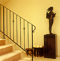 A bronze sculpture is silhouetted against the pale walls of this entrance hall