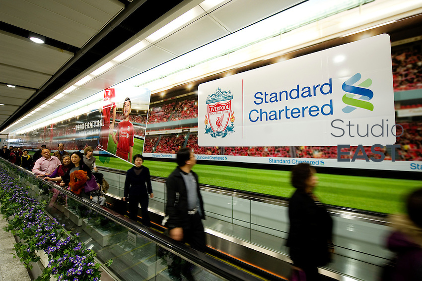 People walk by the giant advertising for Standard Chartered Bank in the Central-HongKong metro underground connection, in Hong Kong, China, on January 27, 2011. Photo by Lucas Schifres/Pictobank