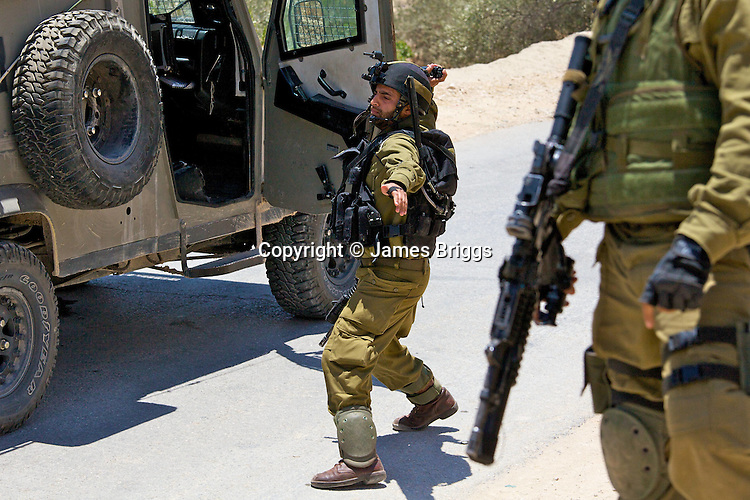 An Israeli army officer throws a concussion grenade in order to disperse protesters during a demonstration against Israel's controversial separation barrier in the West Bank town of Beit Jala near Bethlehem on 04/07/2010.