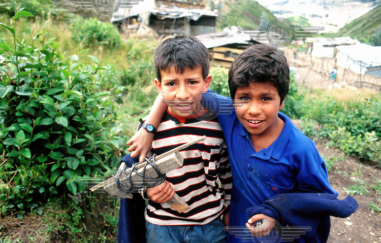 © Paul Smith/Panos Pictures..COLOMBIA: Bogot·.Two children, one with a toy pistol the other with a home-made toy mini-uzi, in a poor neighbourhood in the south of the city.