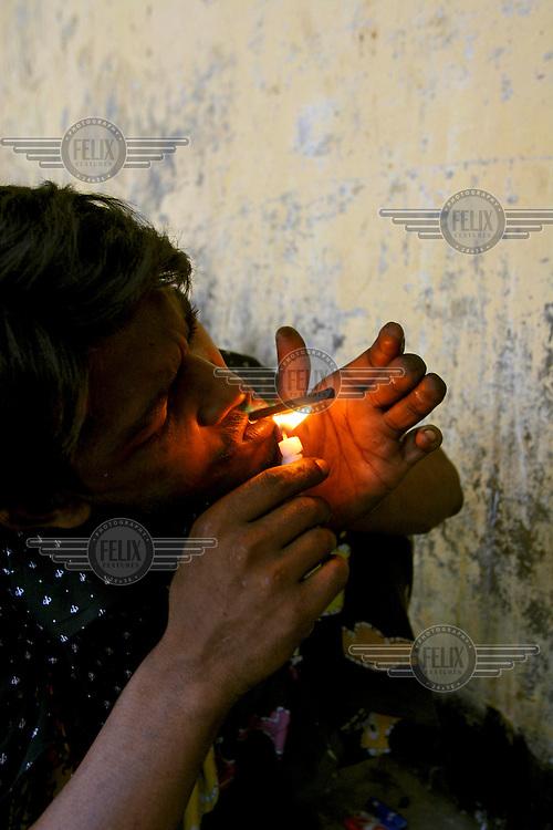A drug addict from a slum community smokes heroin.