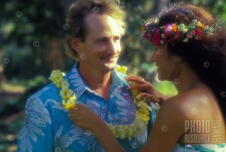 Tourist arriving to Hawaii receiving a plumeria lei greeting from an island woman