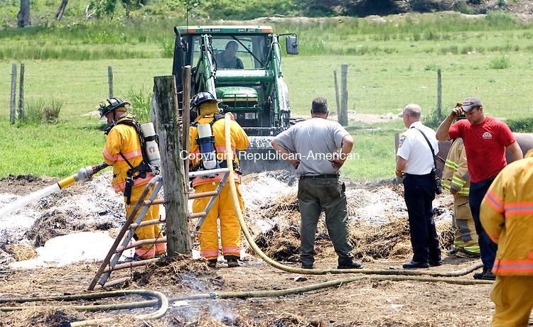 WATERTOWN CT. 21 June 2013-062113SV04-Firefighters extinguish the remains of a hay wagon that caught fire at 360 Sandbank Road in Watertown Friday. The wagon was in a barn but was pulled out before the barn could catch fire. <br /> Steven Valenti Republican-American