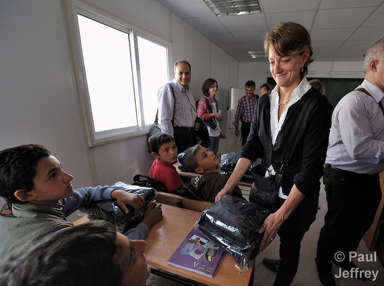 Lisa Henry, the humanitarian response coordinator for Danchurchaid, hands over a school uniform to a boy in the Zaatari Refugee Camp, located near Mafraq, Jordan. Opened in July, 2012, the camp holds upwards of 50,000 refugees from the civil war inside Syria, but its numbers are growing. International Orthodox Christian Charities and other members of the ACT Alliance are active in the camp providing essential items and services.