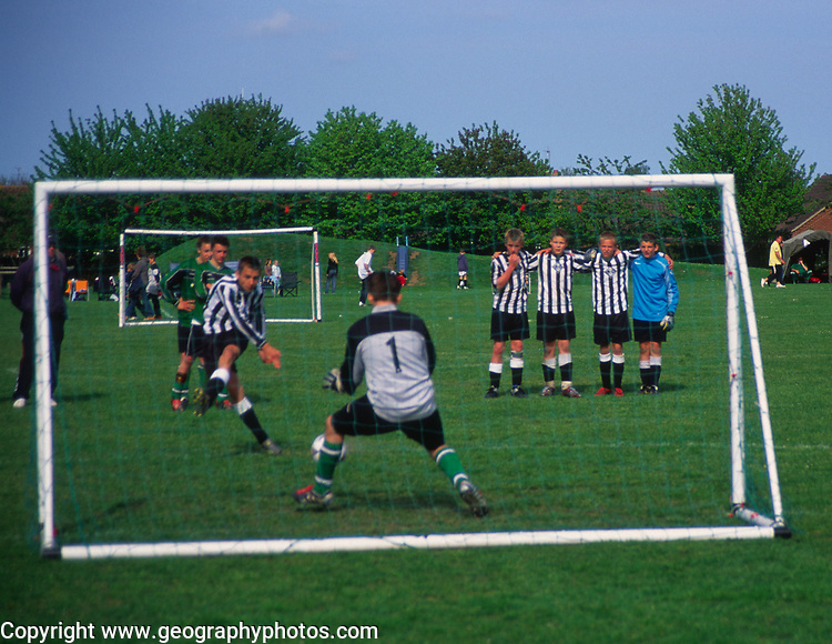 AF5GM7 Children's football tournament. View of goalkeeper from behind the net. Penalty shoot out.