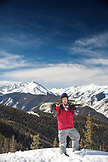 USA, Colorado, Aspen, portrait of a snowboarder at the top of the gondola at Aspen Ski Resort, Ajax, the Elk Mountains in the distance