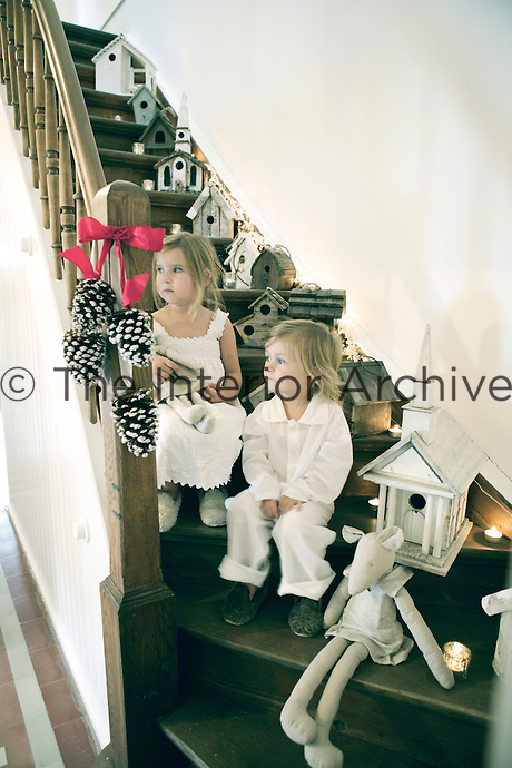 A little girl and boy sitting on the staircase in their night clothes on Christmas morning