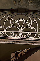 Detail of wrought-iron metalwork above the main entrance door to a building