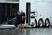 Sept. 2, 2012; Clermont, IN, USA: Crew members for NHRA pro stock driver Chris McGaha walk through the flooded pits as they load equipment into their hauler following the cancellation of qualifying for the US Nationals at Lucas Oil Raceway due to rain. Mandatory Credit: Mark J. Rebilas-