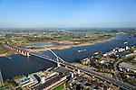 Nederland, Gelderland, Nijmegen, 24-10-2013; de nieuwe stadsbrug van Nijmegen over rivier de Waal, De Oversteek. Daarachter de spoorbrug met fietspad (De Snelbinder) en de laatste brug is de Waalbrug. Links van de rivier grondwerkzaamheden voor de Dijkteruglegging Lent (Ruimte voor de Rivier) en Nijmegen-Noord.<br /> First bridge the new city bridge of Nijmegen on the river Waal, De Oversteek (The Crossing). Next the railway bridge with cycle path (De Snelbinder = The Luggage strap) and finally the Waal bridge. To the left of the river groundwork for the Dike relocation of Lent (project Ruimte voor de Rivier: Room for the River). <br /> luchtfoto (toeslag op standaard tarieven);<br /> aerial photo (additional fee required);<br /> copyright foto/photo Siebe Swart.<br /> luchtfoto (toeslag op standaard tarieven);<br /> aerial photo (additional fee required);<br /> copyright foto/photo Siebe Swart.