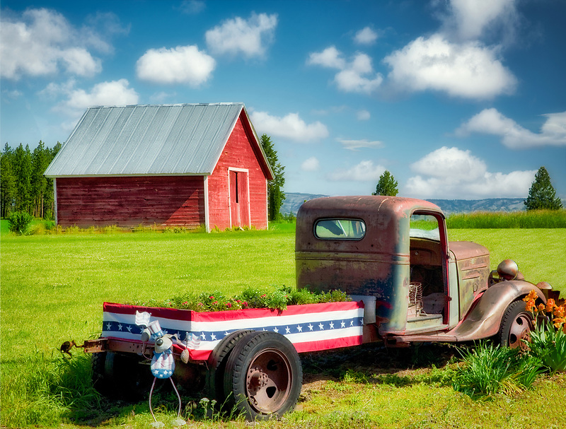 Old truck with flowers and barn. Near flora, Oregon
