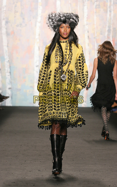 NOAMI CAMPBELL.Anna Sui Fashion Show, Fall 2005, .February 9th 2005.full length catwalk fishnets black boots yellow and black jacket coat fur hat.www.capitalpictures.com.sales@capitalpictures.com.Supplied by Capital Pictures.