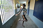 Bouncing a soccer ball in the hallway, a boy who works as a scavenger in the municipal garbage dump in Chennai, India, is hosted in a nearby night shelter by the Madras Christian Council of Social Service.