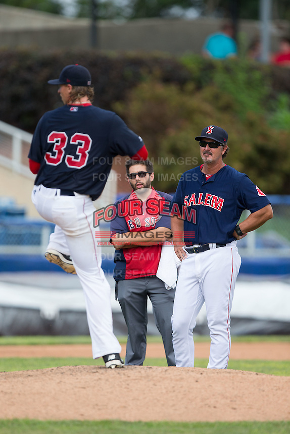 Salem Red Sox pitching coach Paul Abbott (44) and trainer Nick Kuchwara watch starting pitcher Michel Kopech (33) throw a pitch during the game against the Lynchburg Hillcats at LewisGale Field at Salem Memorial Baseball Stadium on August 7, 2016 in Salem, Virginia.  The Red Sox defeated the Hillcats 11-2.  (Brian Westerholt/Four Seam Images)
