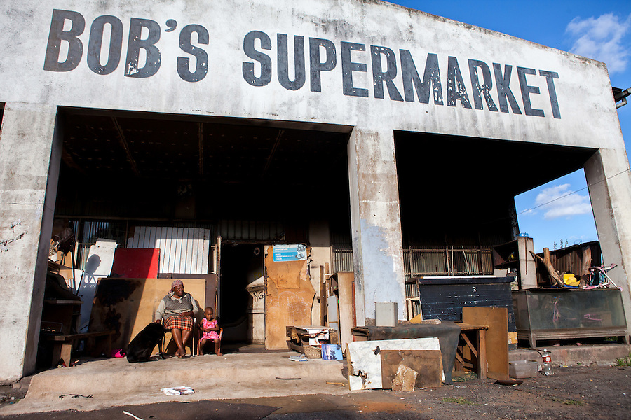 A woman sits with her granddaughter and dog outside an abandoned gold mining grocery store which they and many other families have made their home on the outskirts of Johannesburg, South Africa. . The grocery store's residents have partitioned off the interior space to create privacy for the many families that live there.
