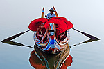 Monks with red umbrellas are rowed across the Irrawaddy River, Mandalay, Myanmar