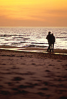 A couple walks on the Lake Michigan shore at sunset, Indiana Dunes National Lakeshore, Indiana
