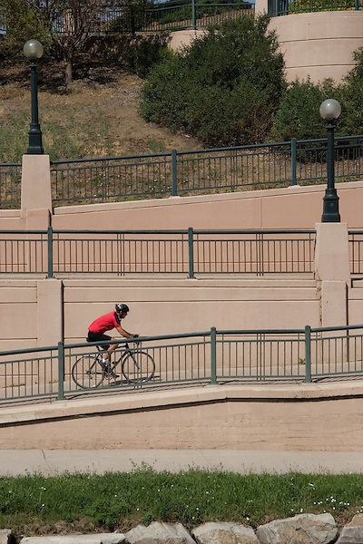 Caucasian man biking along the pathway in Confluence Park, Denver, Colorado. .  John offers private photo tours in Denver, Boulder and throughout Colorado. Year-round.