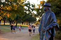 Stevie Ray Vaughan Statue overlooks Auditorium Shores as runners and joggers pass by, Austin, Texas, USA.