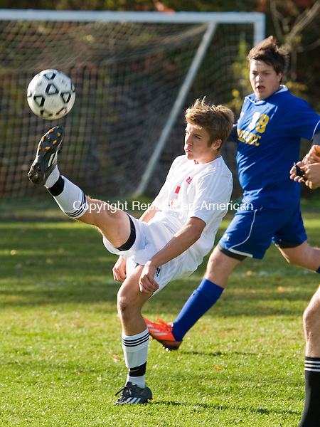 LITCHFIELD, CT-9 October 2014-100914EC04--   Wamogo's Ryan DeLello kicks the ball Thursday while Housatonic's Seth Sherwood watches from behind in Litchfield. Erin Covey Republican-American