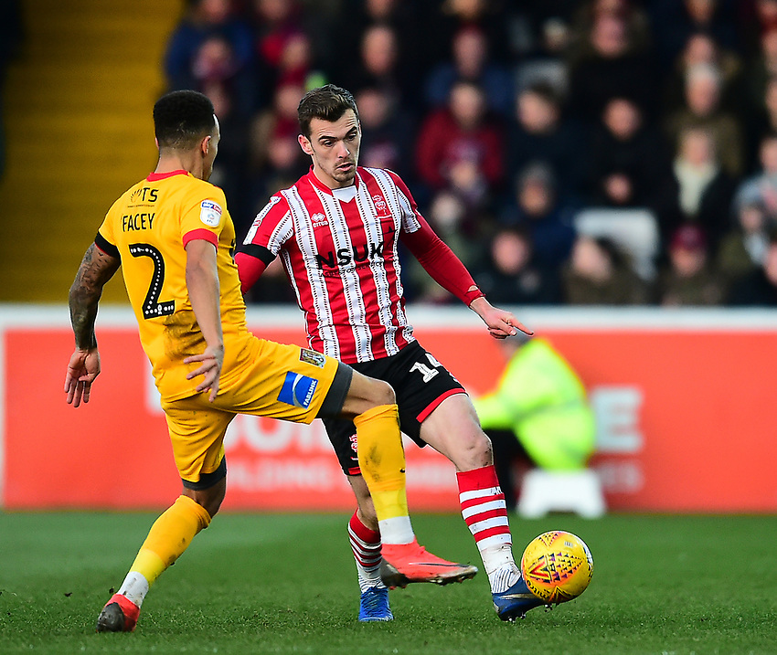 Lincoln City's Harry Toffolo clears under pressure from Northampton Town's Shay Facey<br /> <br /> Photographer Andrew Vaughan/CameraSport<br /> <br /> The EFL Sky Bet League Two - Lincoln City v Northampton Town - Saturday 9th February 2019 - Sincil Bank - Lincoln<br /> <br /> World Copyright © 2019 CameraSport. All rights reserved. 43 Linden Ave. Countesthorpe. Leicester. England. LE8 5PG - Tel: +44 (0) 116 277 4147 - admin@camerasport.com - www.camerasport.com
